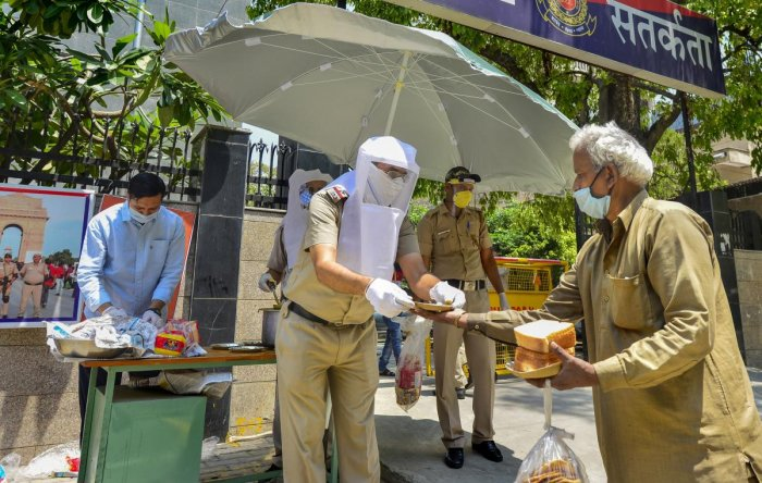 Policemen distribute food among the needy, during the nationwide lockdown to curb the spread of coronavirus, in New Delhi, Monday, April 27, 2020. (PTI Photo)