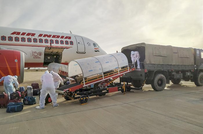 Workers unload the luggage of Indian nationals evacuated from Iran at Jaisalmer Military Station. Two Air India flights carrying over 230 Indians from coronavirus-hit Iran landed here on Sunday morning. (PTI Photo)