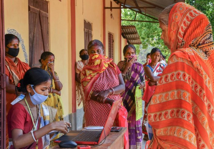 Benficrairies stand in a queue to withdraw money using the mobile bank service introduced by State Bank of India during the nationwide lockdown, in wake of the coronavirus pandemic, in Dharmanagar, North Tripura, Thursday, April 16, 2020. (PTI Photo)