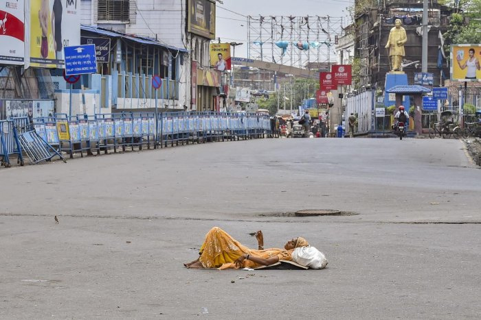 A homeless woman rests in the middle of a deserted road outside the Howrah station in Kolkata on Sunday. PTI