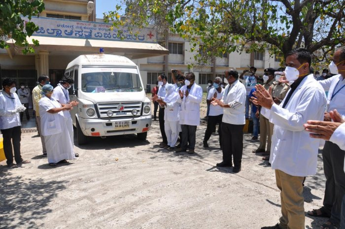 Doctors and other medical staff clap as the vehicle ferrying the first Covid-19 recovered patient leaves district hospital in Vijayapura on Sunday. DH Photo