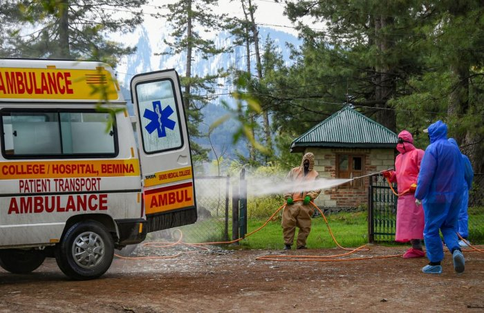 Health officials spray disinfectant on an ambulance that ferried the body of a 72-year-old man who died due to coronavirus, at Tangmarg in Baramulla District of North Kashmir, Saturday, April 25, 2020. (PTI Photo)