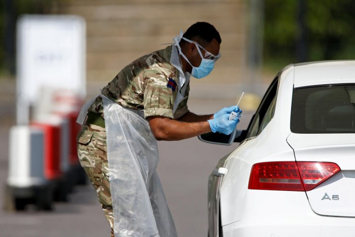 A member of the military conducts a coronavirus disease (COVID-19) check-up at a drive-thru testing site in Chessington, London, Britain, April 24, 2020. Credit: Reuters File Photo