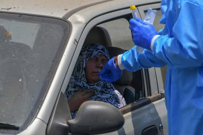A doctor (R) collects a nasal swab from a woman sitting inside a car at a Drive-thru Collection Point Test Centre during a government-imposed nationwide lockdown as a preventive measure against the spread of the COVID-19 coronavirus in Mumbai on April 27, 2020. Credit: AFP Photo