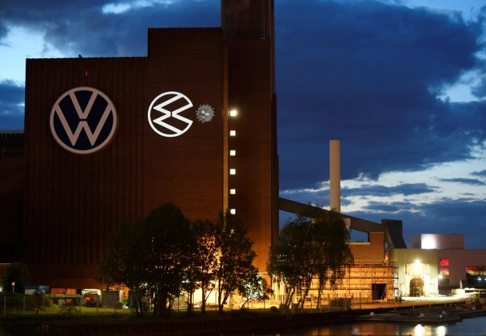 A cartoon of a VW logo squashing the coronavirus is displayed on a building at Volkswagen's headquarters. Reuters/File photo