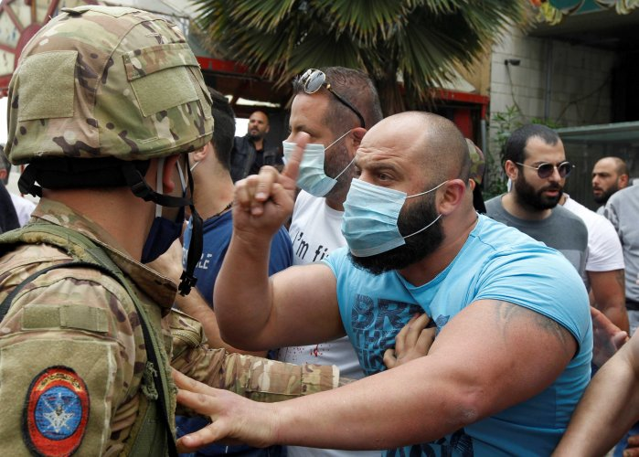 A Lebanese demonstrator gestures to a Lebanese soldier, during a protest against the collapsing Lebanese pound currency and the price hikes, in Zouk, north of Beirut, Lebanon. (Reuters photo)
