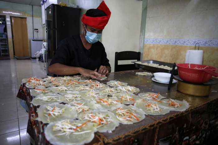 """An online Ramadan bazaar trader wraps """"Popiah"""" spring rolls at his home, during the movement control order due to the outbreak of the coronavirus disease (COVID-19), in Sungai Buloh, Malaysia. (Reuters)"""