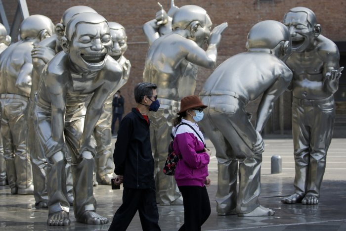 People wearing protective face masks to help curb the spread of the new coronavirus walk by human sculptures on display outside an art gallery in Beijing. (Credit: AP Photo)