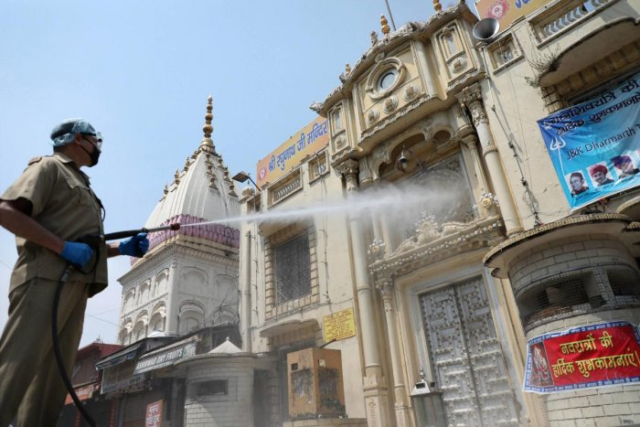 A firefighter sprays disinfectant at Raghunath Bazaar area during a nationwide lockdown in the wake of coronavirus pandemic, in Jammu, Saturday, April 25, 2020. (PTI Photo)