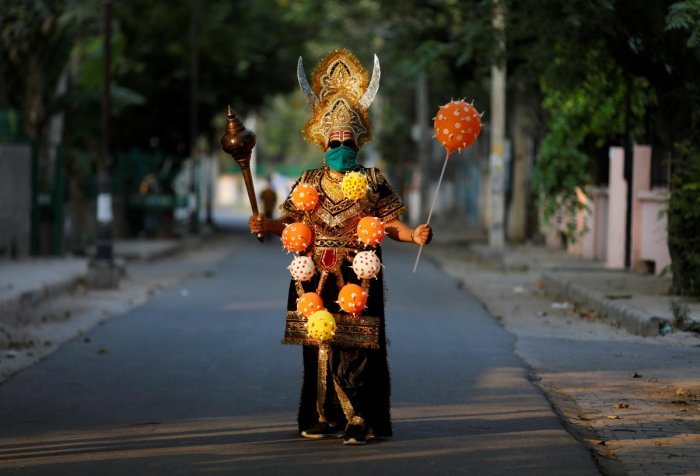 A local resident dressed as Yamraj or Hindu god of death, wearing a novel coronavirus-themed balloon necklace, gestures as he poses during an awareness about social distancing and staying at home organised by Delhi police during a nationwide lockdown to slow the spreading of the coronavirus disease (COVID-19), in New Delhi, India, April 28, 2020. Credit: Reuters Photo