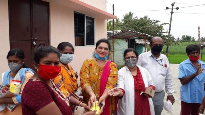 Vice president of Human Rights Committee Neena Patel and others distribute food supplements and nutritious food to residents of B T Lalitha Naik Layout in Mandya on Tuesday.