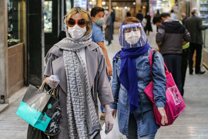 Shoppers clad in protective gear, including face masks and shields and latex gloves, due to the COVID-19 coronavirus pandemic, walk through the Tajrish Bazaar in Iran's capital Tehran on April 25, 2020. Credit: AFP Photo