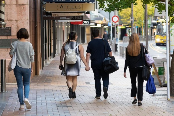 People walk down a street on the first day of the easing of restrictions in Wellington. AFP