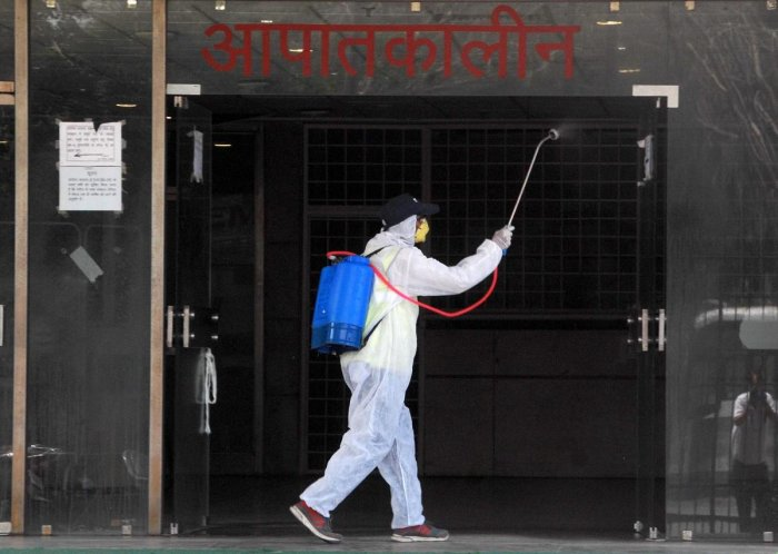 A health worker sanitises outside the emergency ward of Super Speciality Paediatric Hospital & Post Graduate Teaching Institute, during the nationwide lockdown to curb the spread of coronavirus, at Sec-30 in Noida, Tuesday, April 28, 2020. Credit: PTI Photo