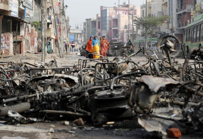 Women walk past charred vehicles in a riot affected area following clashes between people demonstrating for and against a new citizenship law in New Delhi. Credit: Reuters Photo