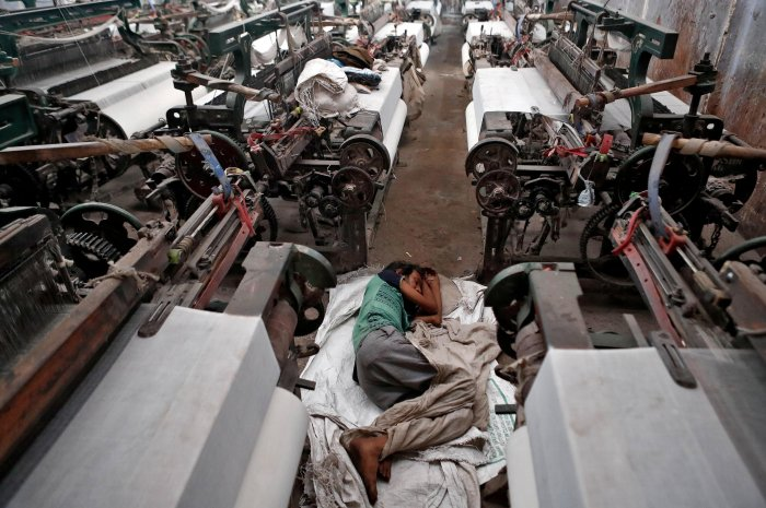 A migrant worker, who works in a textile loom, rests inside a loom after it was shut due to the lockdown. (Credit: Reuters Photo)