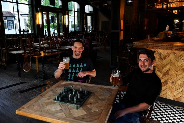 Steve Pond and Dominic Townsend enjoy a pint of beer and a game of chess at The Prince, a pub they share an apartment above and say are lucky enough to be stuck in during lockdown as the coronavirus disease (COVID-19) continues in London, Britain. (Reuters)