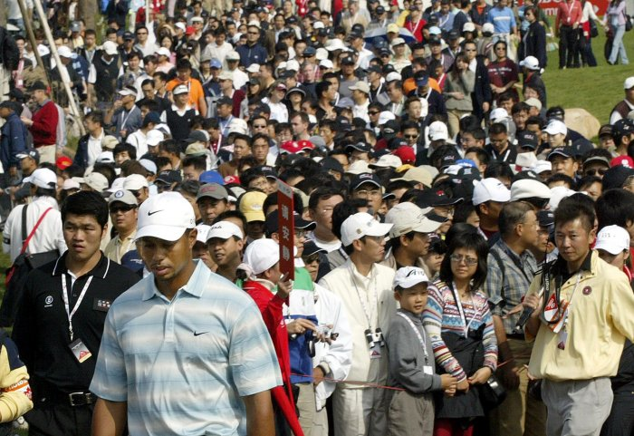 This file photo taken on November 12, 2005 shows US golfer Tiger Woods (front L, in white hat) being followed by a large crowd of Chinese spectators as he walks from the tee-off area during the HSBC Champions golf tournament in Shanghai. (Credit: AFP)