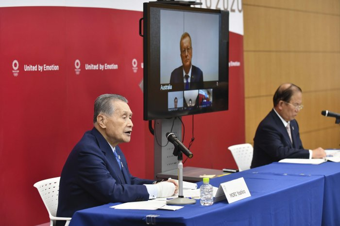 Tokyo 2020 Organizing Committee President Yoshiro Mori, left, and CEO Toshiro Muto, right, attend teleconference with International Olympic Committee member John Coates. (AP Photo)