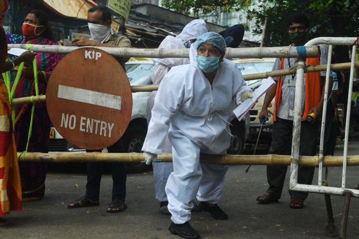 A municipal worker wearing a hazmat suits crosses a barrier during a door to door survey on residential area during a government-imposed nationwide lockdown as a preventive measure against the COVID-19 coronavirus, in Kolkata on April 29, 2020. Credit: AFP Photo