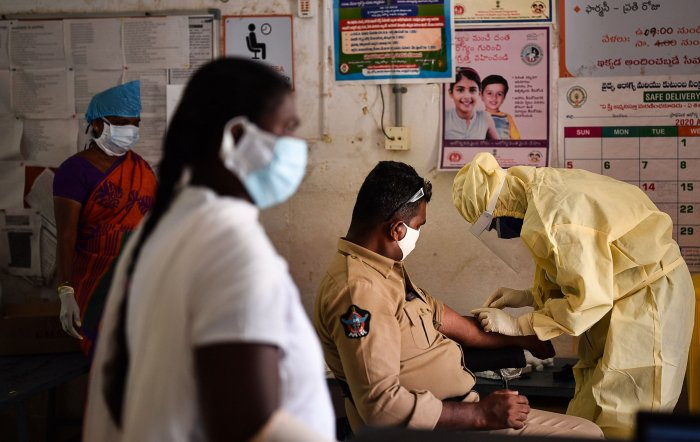 A healthcare worker takes blood sample of a policeman for COVID-19 test in wake of the coronavirus pandemic, in Vijayawada. (PTI Photo)