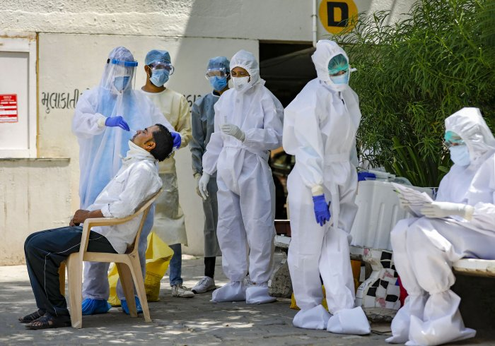 A team of medics collect swab sample of a resident for COVID-19 test after many positive coronavirus cases were detected in the area, during the nationwide lockdown, in Ahmedabad. (PTI Photo)