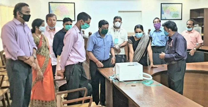 Representatives of Vivekananda College of Engineering and Technology, Puttur, explain the functioning of the low-cost respiratory support device to Deputy Commissioner Sindhu B Rupesh in Mangaluru. Credit: DH Photo