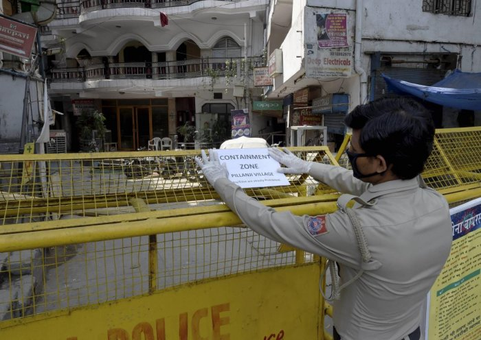 :A security guard pastes a notice on a barricade at Pilanji village area, identified as a COVID-19 containment zone, during the nationwide lockdown to curb the spread of coronavirus, in New Delhi, Tuesday, April 28, 2020. (PTI Photo)