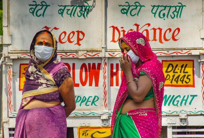 Women wearing masks maintain social distance in a market, during the nationwide lockdown to curb the spread of coronavirus, in New Delhi, Monday, April 27, 2020. Credit: PTI Photo