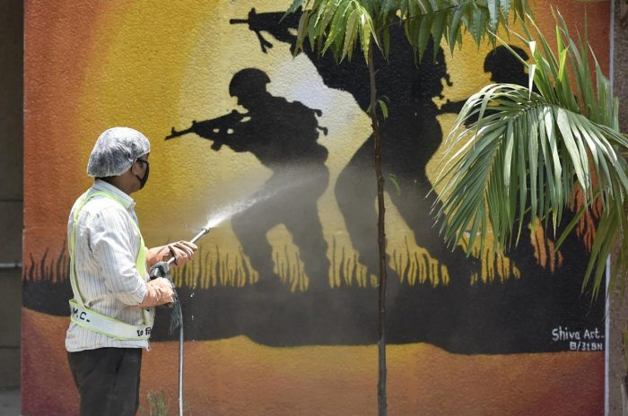An East Delhi Municipal Corporation (EDMC) worker sprays disinfectant on a wall at CRPF Camp Mayur Vihar, during a nationwide lockdown to curb the spread of coronavirus, in New Delhi, Wednesday, April 29, 2020. Credit: PTI Photo