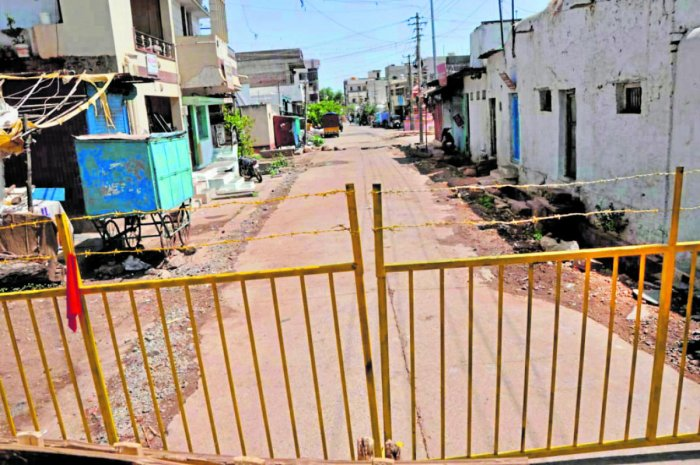 The street where a Covid-19 case was detected is barricaded in Gadag on Tuesday. DH Photo