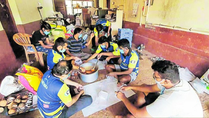 The members of the Padutirupathi cricket team pack the food they have cooked.