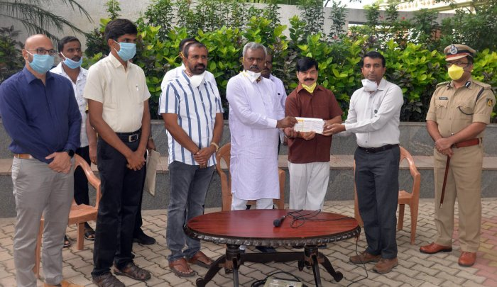 District In-charge Minister S T Somashekar presents a cheque to Executive Director of Mysuru Zoo on Wednesday. MCC Commissioner Gurudatta Hegde, DC Abhiram G Sankar MLAs L Nagendra and S A Ramdas are seen. DH PHOTO