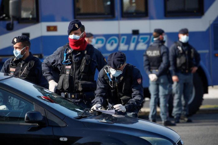 Police officers wearing protective face masks check documents of drivers, during the coronavirus disease (COVID-19) outbreak in Ostia, near Rome, Italy. Credit: Reuters File Photo
