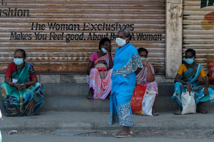 Women wearing facemasks sit in front closed shops during a government-imposed nationwide lockdown as a preventive measure against the COVID-19 coronavirus, in Chennai on April 21, 2020. Credit: AFP Photo