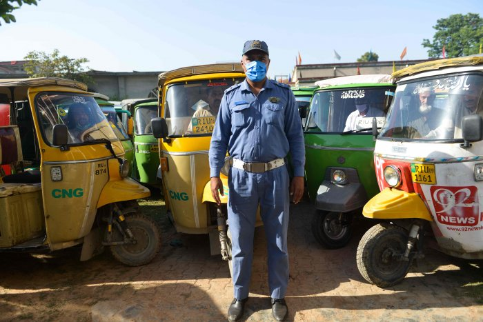 A traffic policeman stands next to rickshaws at a food distribution organised by the traffic police during a government-imposed nationwide lockdown as a preventive measure against the COVID-19 coronavirus, in Rawalpindi. (AFP Photo)