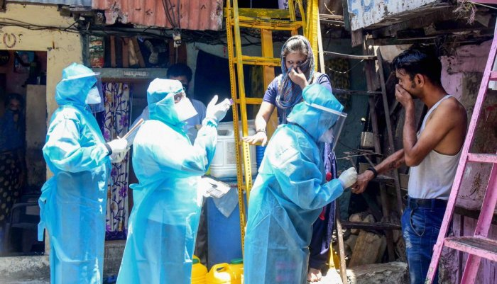 Health workers wearing protective suits screen resident of Kumbharwada during a house-to-house health survey, after detection of some COVID-19 positive cases, during the nationwide lockdown, at Dharavi in Mumbai, Wednesday, April 29, 2020. (PTI Photo)