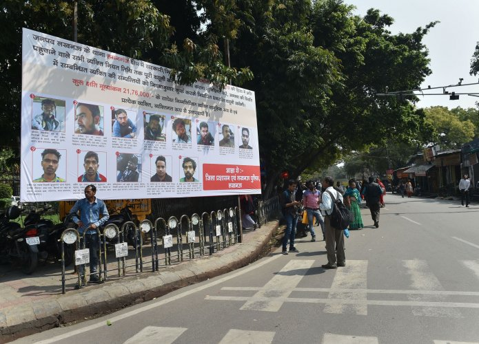 People walk past a poster displaying photographs of those who have been identified to pay the compensation for vandalizing public properties during protests against CAA, in Lucknow. (Credit: PTI)