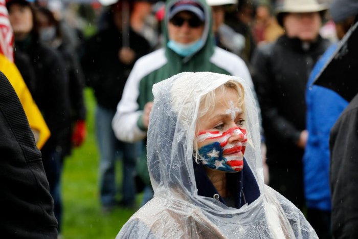 A protestor with an upside down flag painted on her face stands at an American Patriot Rally organized by Michigan United for Liberty protest for the reopening of businesses, on the steps of the Michigan State Capitol in Lansing, Michigan on April 30, 2020. Credit: AFP Photo