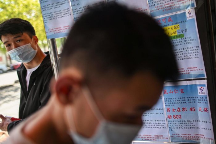 Men wearing face masks are seen next to papers with new job offers in an employment agency in Shanghai. AFP