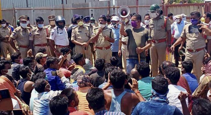 Police officials appeal to protesting migrant workers to maintain calm at IIT Hyderabad, Kandi, Wednesday, April 29, 2020. Peeved over denial of wages, hundreds of migrant workers working at IIT Hyderabad in neighbouring Sangareddy district today allegedly attacked some officials of construction companies and threw stones damaging a police vehicle and injuring a Sub-Inspector and two policemen. (PTI Photo)