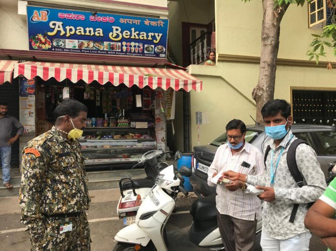Marshals imposing a fine on an offender for littering at MSR Nagar in Bengaluru.