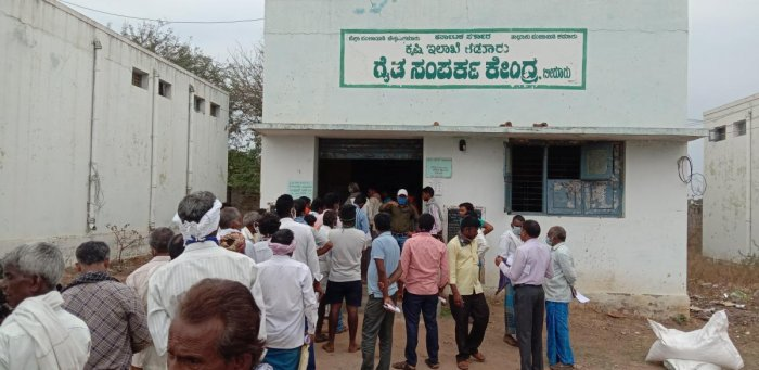 Farmers wait outside the Raitha Samparka Kendra to purchase seeds for cultivation in Birur. DH Photo