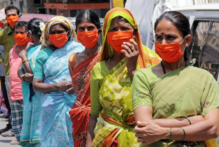 Women wearing masks stand in a queue to collect ration kits distributed during the nationwide lockdown imposed in wake of the coronavirus pandemic, in Bengaluru, Thursday, April 30, 2020. (PTI Photo)