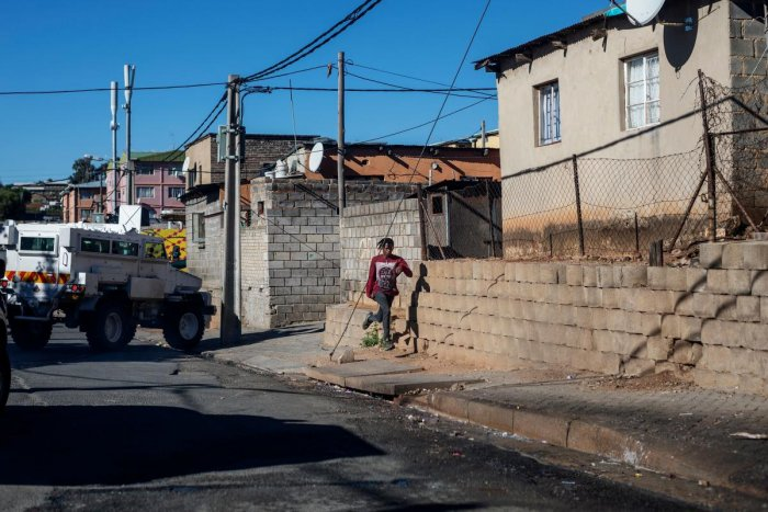 A boy runs away during a mixed patrol of South African National Defence Force (SANDF) and South African Police Service (SAPS) in Alexandra township in Johannesburg. AFP