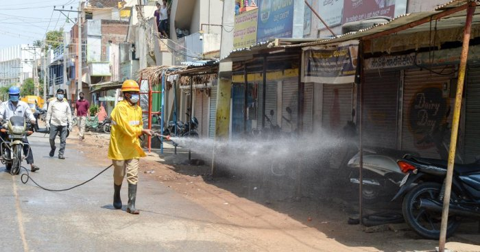 A fire and emergency personnel sprays disinfectant in Jalinagar in Davangere on Thursday after a person tested positive for Covid-19. DH Photo/Satish Badiger