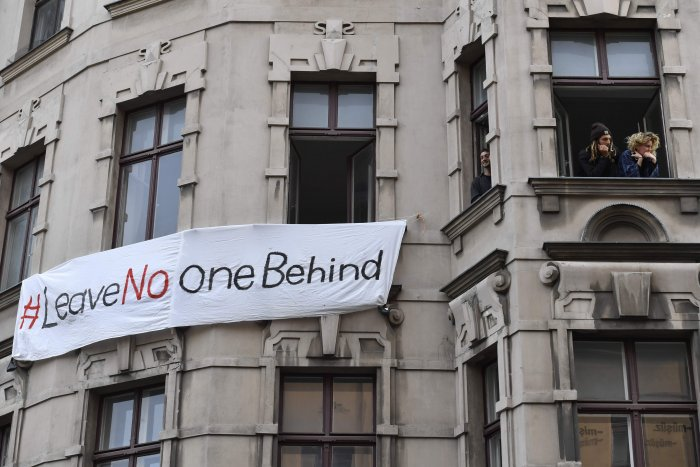 "People look out the window of a house with a banner which reads ""#leave no one behind"" in Berlin's Kreuzberg district on May 1, 2020, during May Day protests amid the COVID-19 outbreak caused by the novel coronavirus. (AFP photo)"