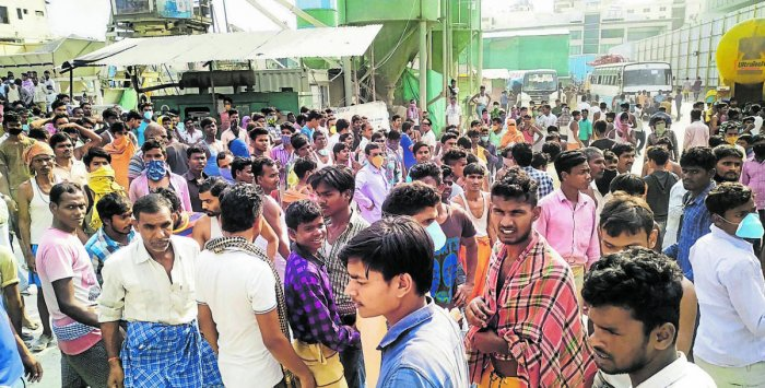 Namma Metro workers gather to stage a protest demanding wages and transportation facilities to return to their home towns. (Credit: DH Photo)