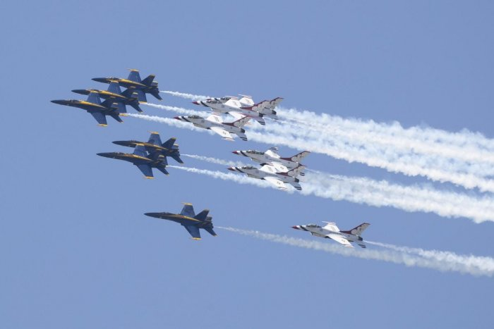 A formation of jets from the Navy's Blue Angels, left, and the Air Force's Thunderbirds fly over Atlanta, to show support for medical workers fighting the coronavirus outbreak