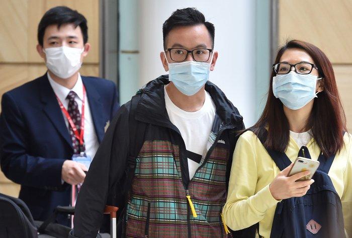 Passangers arrive at Sydney airport wearing masks after landing. (AFP Photo)